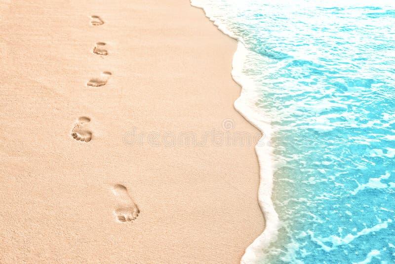 Menschliche Abdrücke auf Strandsand am Erholungsort lizenzfreie stockfotos