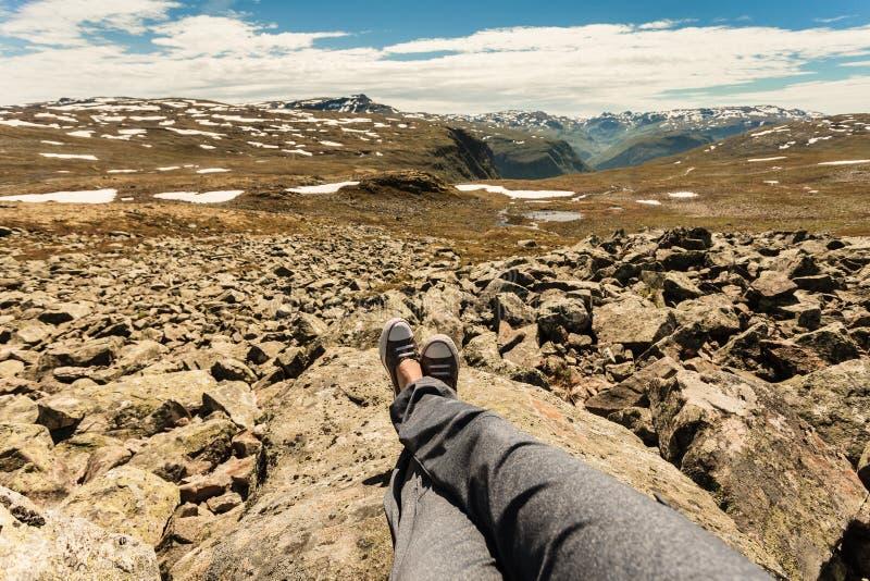 Menschliche Beine und Berge gestalten in Norwegen landschaftlich stockfotografie