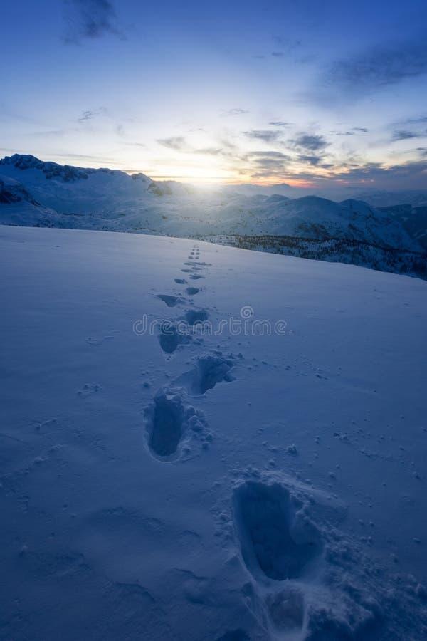 Menschliche Fußspuren im Schnee vor SonnenaufSonnenaufgang auf den Berggipfeln stockbild