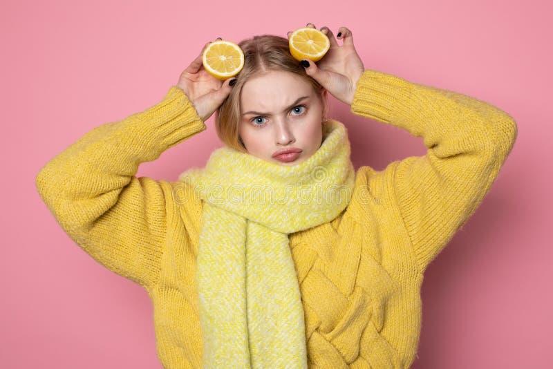 Menschliche Gef?hle Blondes sch?nes europ?isches M?dchen im gelben lustigen Gesicht der Strickjacken- und Schalvertretung, zwei g lizenzfreie stockfotografie