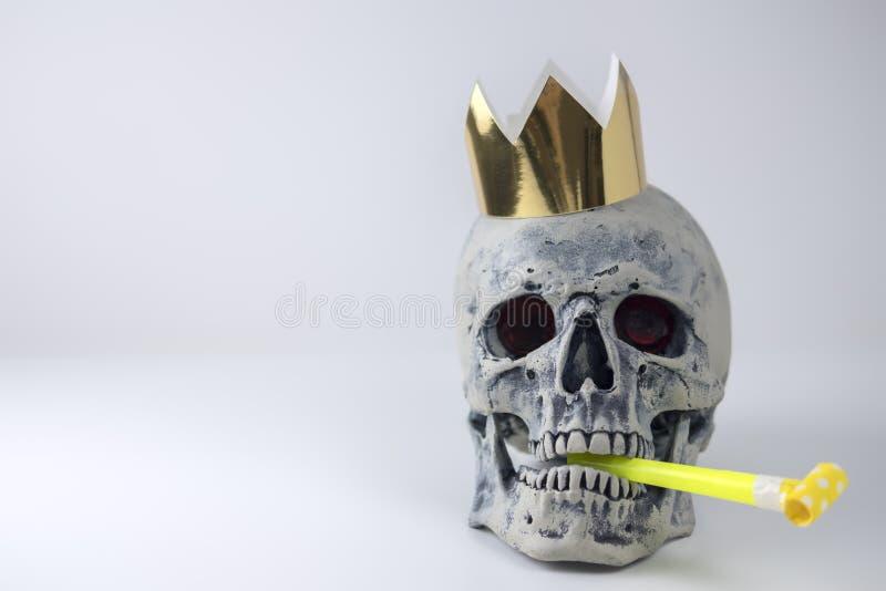 Menschliche graue Schädelnachahmung Halloweens mit festlichem Rohr im Mund und goldener Krone auf Kopf Verzierung für Feiertag stockbild