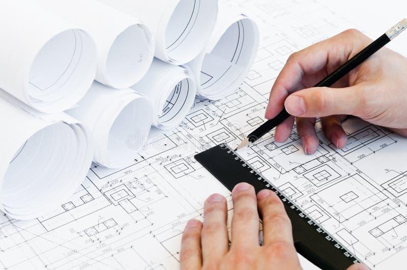 Menschliche Hände, die ein Projekt zeichnen stockbild