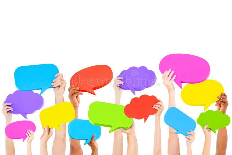 Menschliche Hände, die multi farbige Spracheblasen halten lizenzfreies stockbild