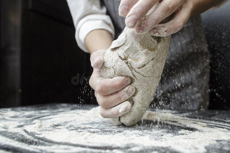 Menschliche Hände kneten den Teig auf einem schwarzen Holztisch lizenzfreie stockbilder
