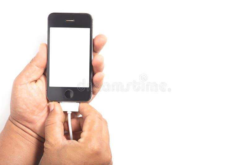 Menschliche Hände schließt Stecker für Aufladungssmartphone an lizenzfreie stockfotografie