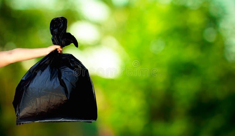 Menschliche Hand, die Abfalltasche zeigt lizenzfreie stockbilder