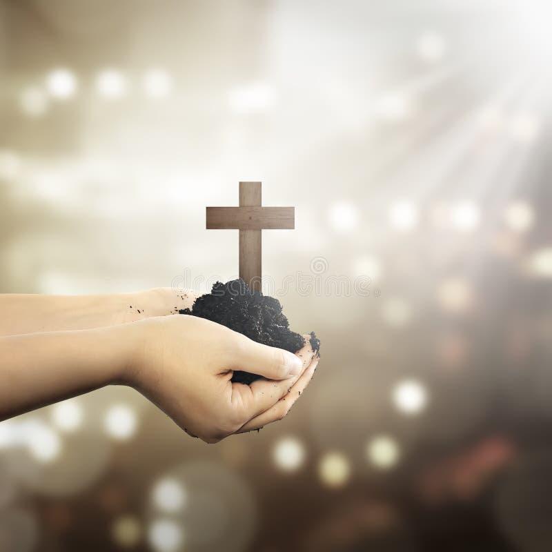 Menschliche Hand, die christliches Kreuz mit Boden auf der Hand hält lizenzfreies stockbild