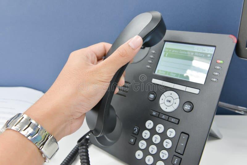 Menschliche Hand, die das Telefon aufhebt stockfoto