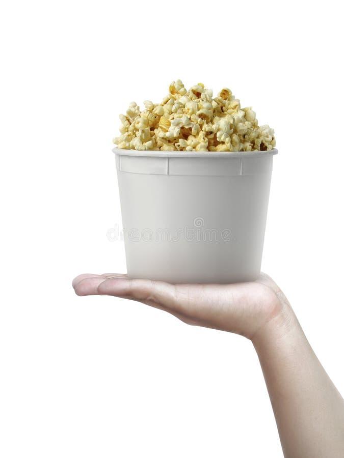 Menschliche Hand, die ein Popcorn lokalisiert auf einem weißen Hintergrund hält lizenzfreie stockbilder