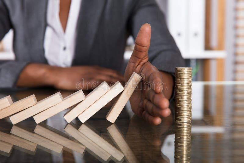 Menschliche Hand, die Holzklötze vom Fallen auf Staplungsmünzen stoppt lizenzfreie stockfotografie
