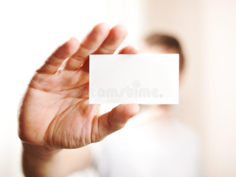 Menschliche Hand, die leere Visitenkarte hält lizenzfreie stockfotografie