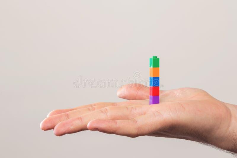 Menschliche Hand mit bunten Ziegelsteinen über einer weißen Wand stockbild