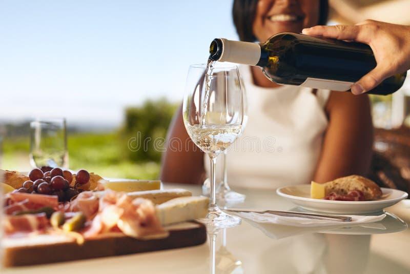 Menschliche Handströmendes Weißwein von einer Flasche stockbild