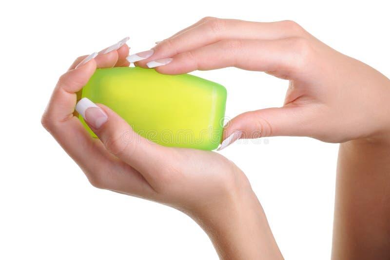 Menschliche weibliche Hände, welche die grüne Seife anhalten lizenzfreies stockfoto