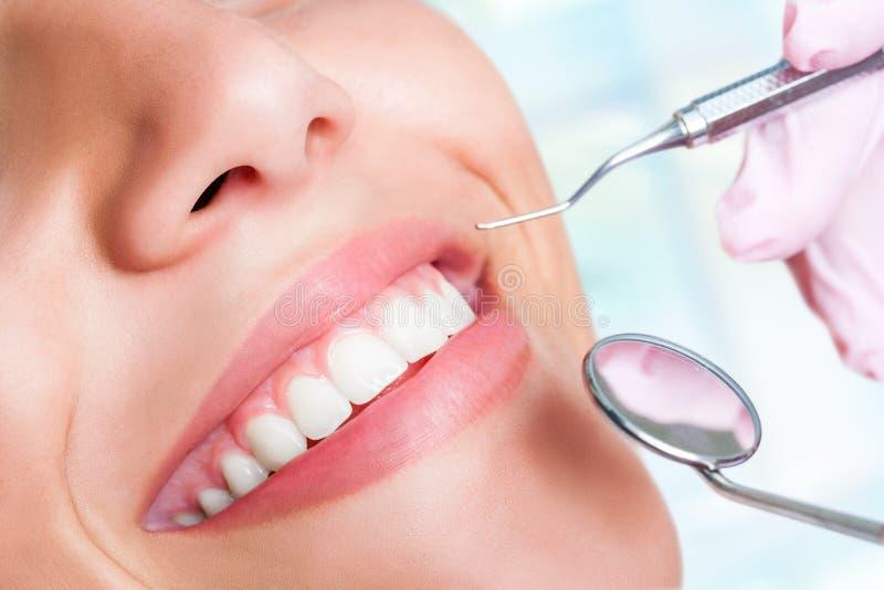 Menschliche Zähne mit Beil und Mundspiegel lizenzfreies stockbild