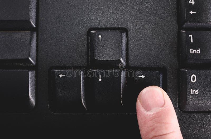 Menschlicher Finger, der die gerichtete rechte Taste von einem schwarzen Schlüssel drückt stockfoto