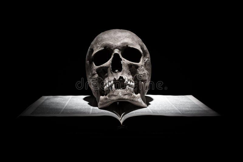 Menschlicher Schädel auf altem offenem Buch auf schwarzem Hintergrund unter Lichtstrahl stockbild