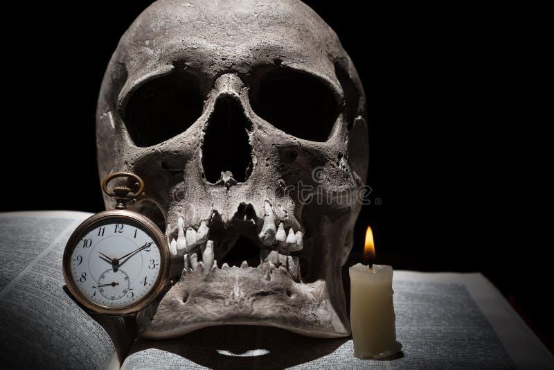 Menschlicher Schädel auf altem offenem Buch mit brennender Kerzen- und Weinleseuhr auf schwarzem Hintergrund unter Lichtstrahl Ab stockfoto