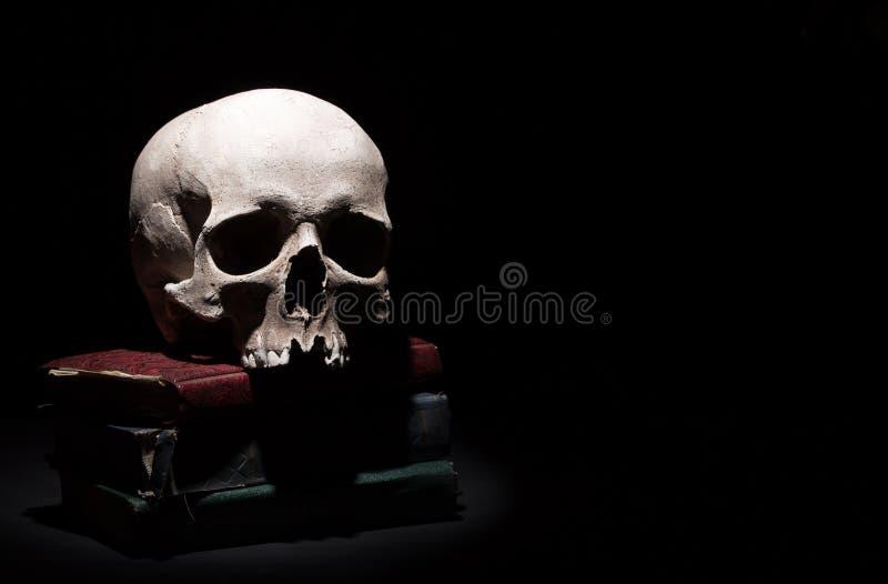 Menschlicher Schädel auf alten Büchern auf schwarzem Hintergrund unter Lichtstrahl Drastisches Konzept lizenzfreie stockfotos