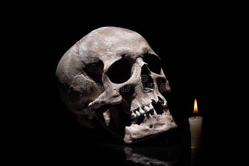 Menschlicher Schädel mit brennender Kerze auf schwarzem Hintergrund mit Reflexionsabschluß oben stockfotografie