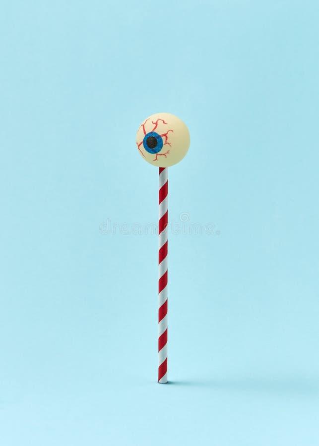 Menschliches Augapfel auf einem Kunststoffstroh als Süßigkeiten stockbilder