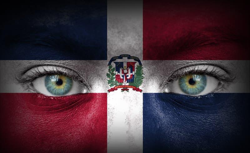 Menschliches Gesicht gemalt mit Flagge von Dominikanischer Republik stockfotografie