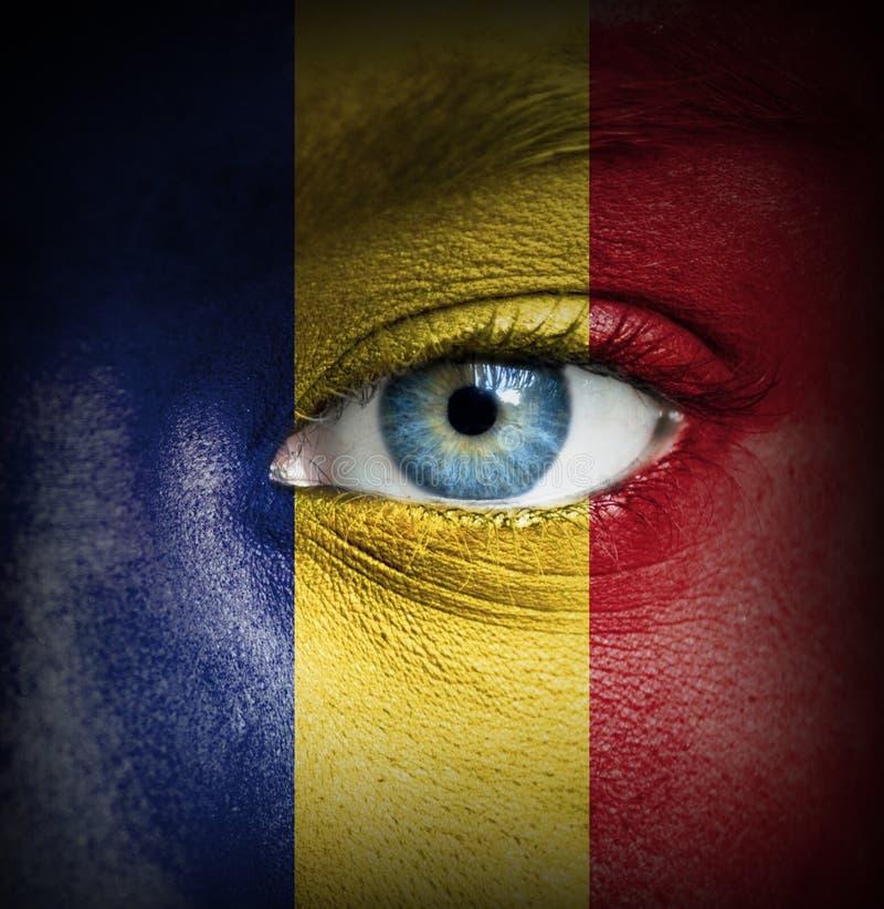 Menschliches Gesicht gemalt mit Flagge von Rumänien lizenzfreie stockfotos