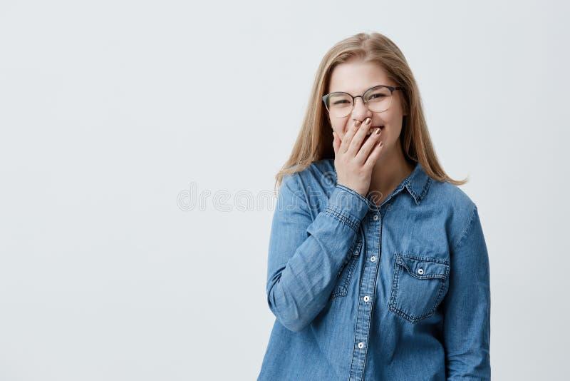 Menschliches Gesichts-Ausdrücke und Gefühle Junge positive und reizend Blondine, die herzlichst über einen lustigen Witz lachen stockfotografie