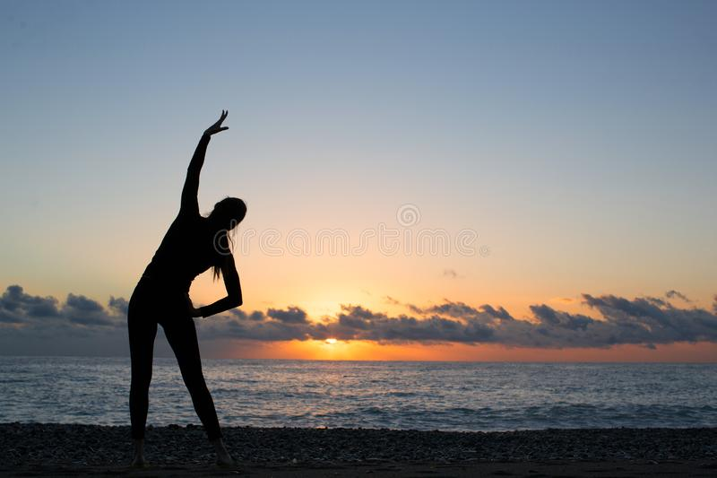 Menschliches Schattenbild, das Aufwärmen auf dem Strand bei Sonnenaufgang tut stockbild
