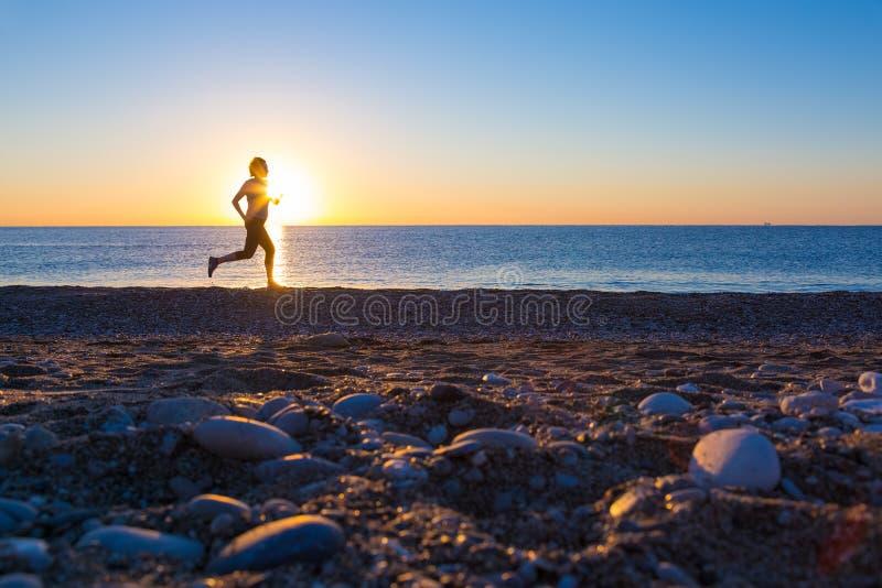 Menschliches Schattenbild, das entlang Ozean-Strand bei Sonnenaufgang rüttelt lizenzfreie stockfotos