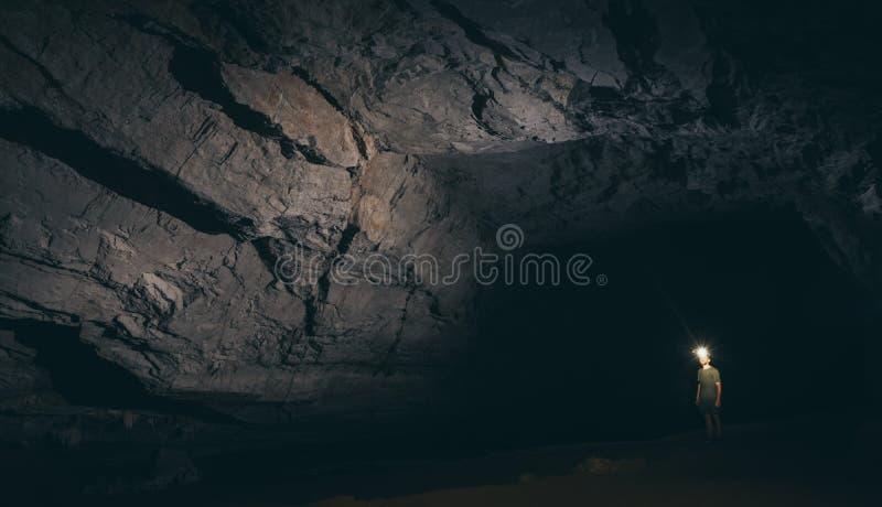 Menschliches Schattenbild steht innerhalb der Wasserhöhle mit Fackel in der Hand in Konglor, Laos stockfoto
