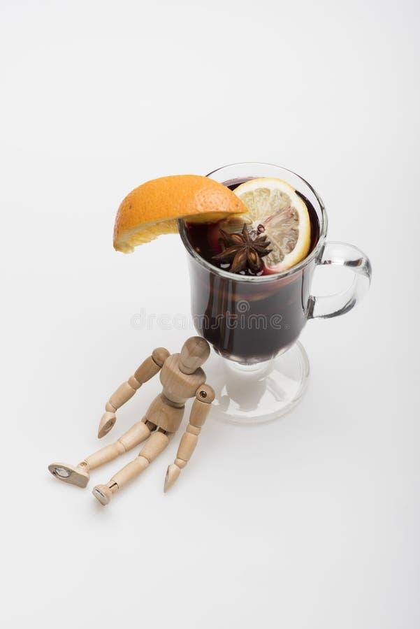 Menschliches Spielzeug sitzt betrunken in der Nähe von Glas Wein stockfotografie