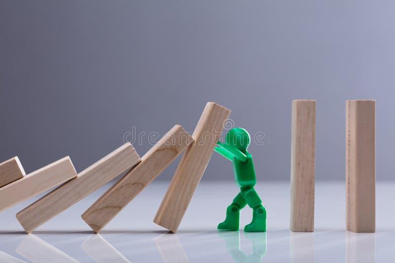 Menselijk Cijfer die Houten Domino'sblokken tegenhouden stock afbeelding