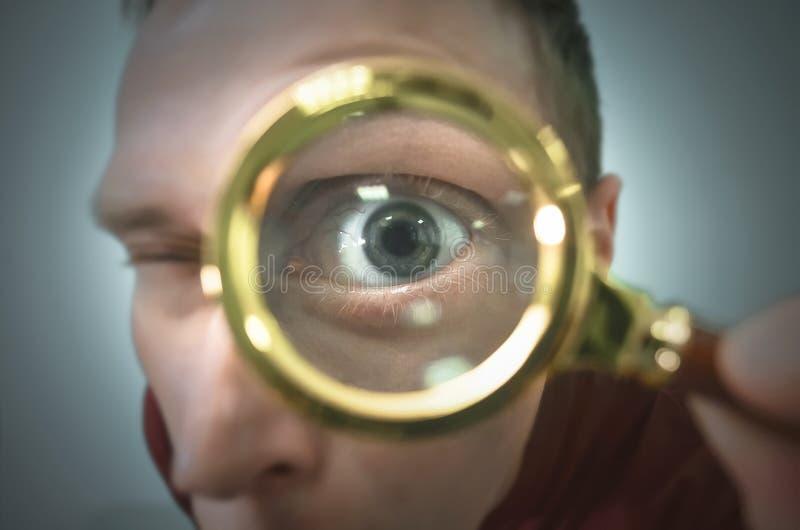 Menselijk oog door een vergrootglas stock foto