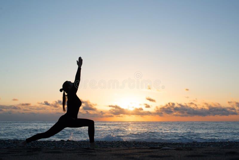 Menselijk silhouet die yoga op het strand voor het toenemen zon doen royalty-vrije stock afbeelding