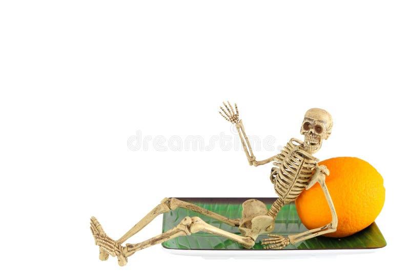 Menselijk skelet die op sinaasappel, het ontspannen leunen stock afbeelding