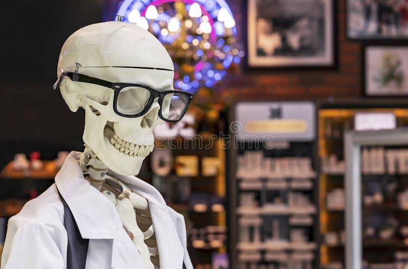 Menselijk skelet in een witte medische toga en zwarte glazen royalty-vrije stock fotografie