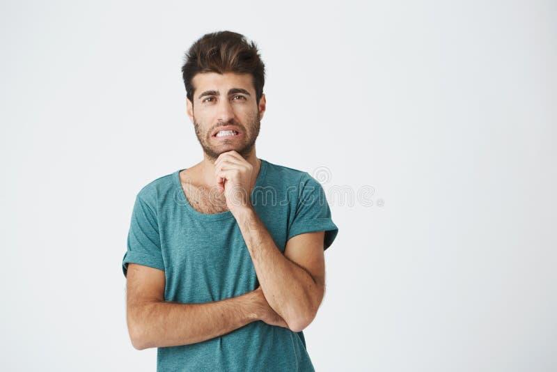 Menselijke gezichtsuitdrukkingen, emoties en gevoel Knappe jonge aantrekkelijke mens die de camera met nadenkend bekijken en stock foto