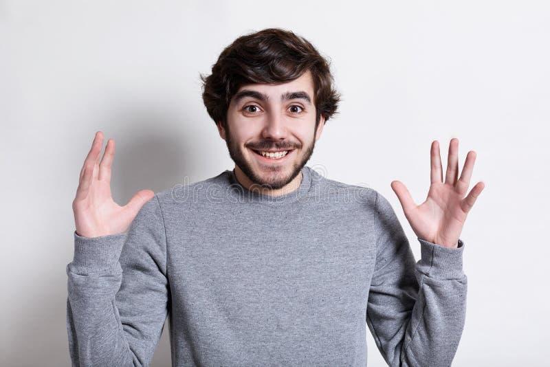 Menselijke Gezichtsuitdrukkingen en Emoties Portret van jonge hipster met baard en modern kapsel die bij camera met wapens glimla stock foto