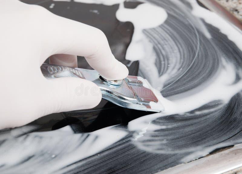 Menselijke hand die een ceramische haardplaat met een schraper schoonmaken stock foto's