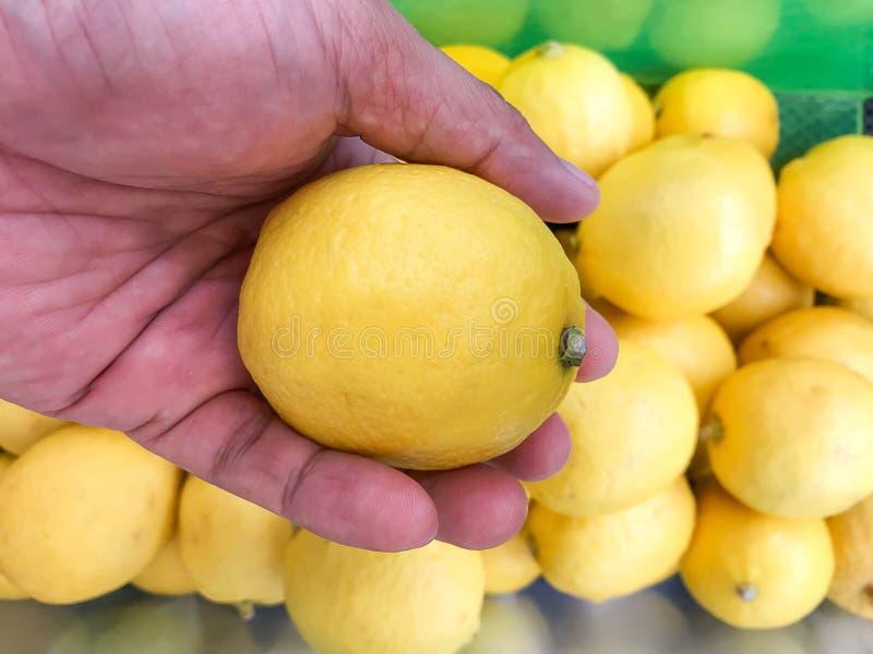 Menselijke hand die een citroen op onduidelijk beeldachtergrond houden royalty-vrije stock afbeelding