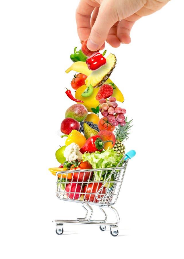 Menselijke hand die een stapel van verse vruchten en groenten zetten in een overvol die boodschappenwagentje op witte achtergrond stock afbeelding