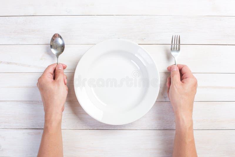 Menselijke hand die een vork en een lepel houden stock foto