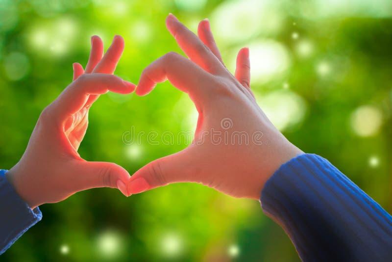 Menselijke hand die het teken van de gebaarliefde op verse groene aard tonen stock foto's
