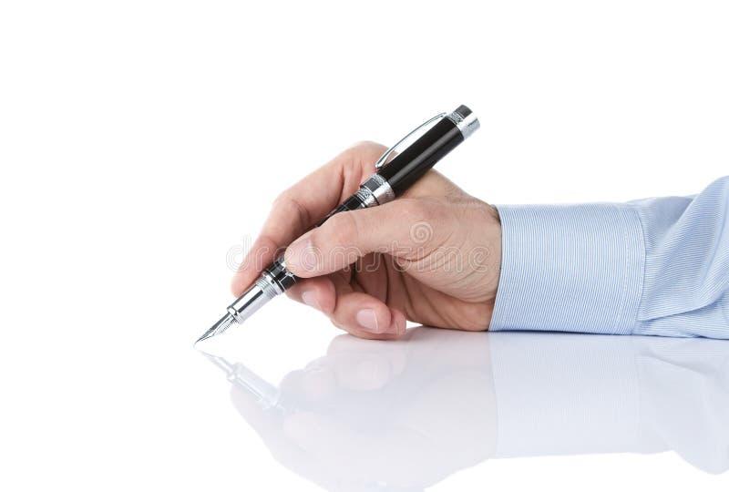 Menselijke hand die met zilveren pen schrijft stock afbeeldingen