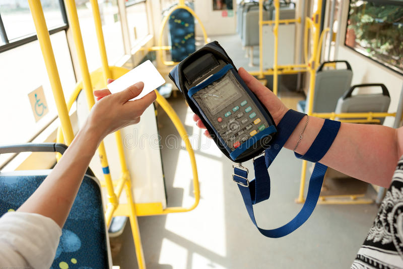 Menselijke hand die plastic kaarten houden De passagier betaalt voor vervoerprijs in openbaar vervoer Betalingsterminal, creditca royalty-vrije stock afbeelding