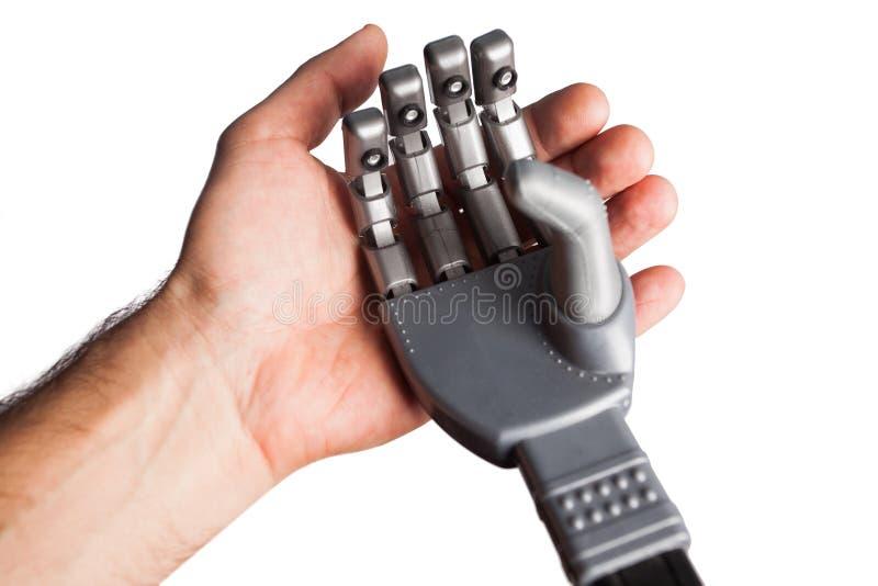 Menselijke hand die robotachtige hand houden stock fotografie