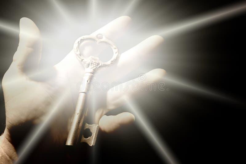 Menselijke hand met een oude sleutel stock foto