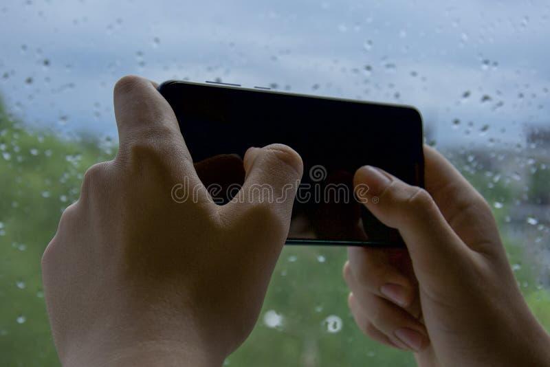 Menselijke handen die de telefoon houden en op het touche screen met uw duimen spelen op de achtergrond van groene aard en blauwe royalty-vrije stock foto