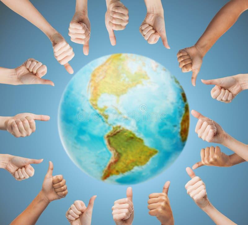 Menselijke handen die duimen in cirkel over aarde tonen stock afbeeldingen